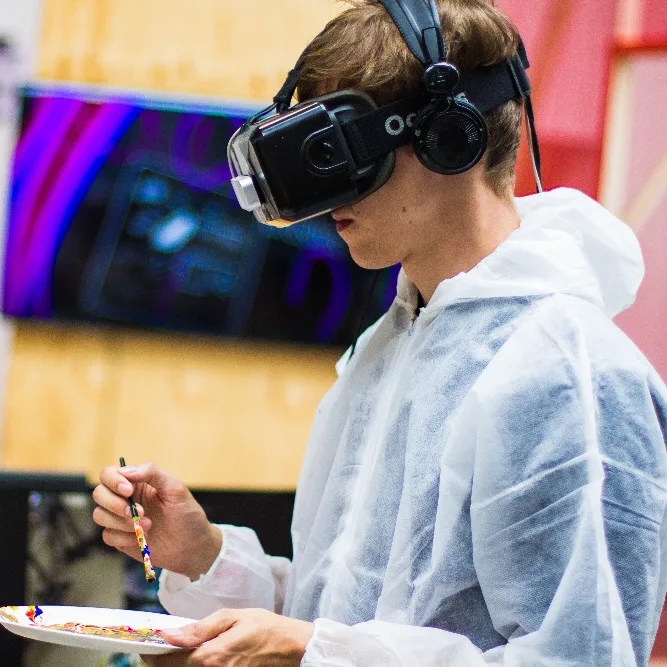 A boy learning how to paint while using a VR headset.